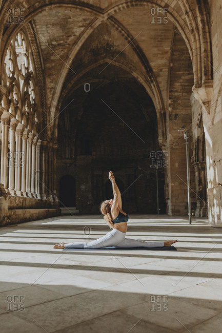 Woman practicing Yoga in old cathedral, Lleida, Spain.