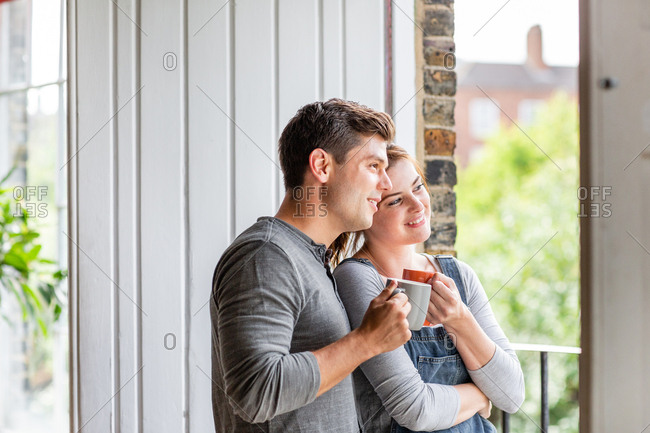 Young adult couple looking out of window in new home