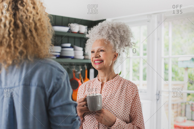 Senior adult woman having coffee with daughter
