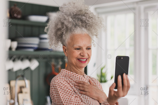 Senior adult woman on a videocall with family