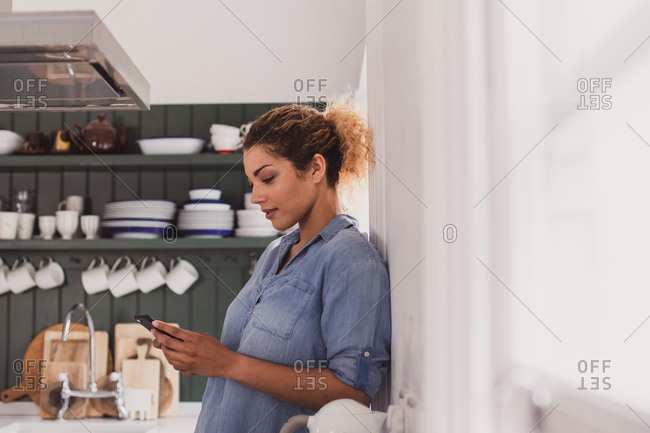 Adult female looking at smartphone in kitchen