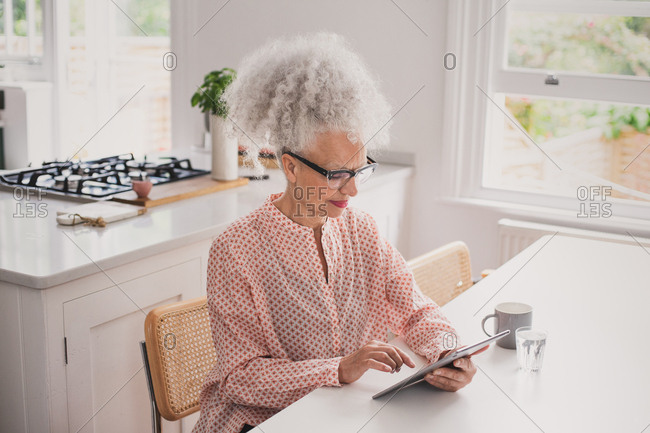Senior adult female looking at digital tablet whilst having morning coffee