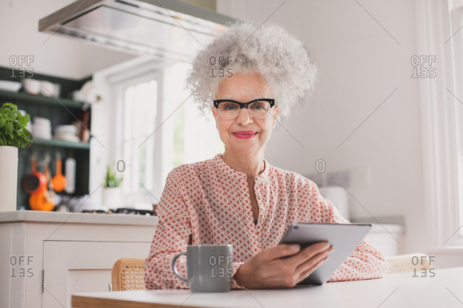 Portrait of senior adult female looking at digital tablet at home