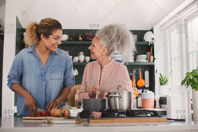 Senior adult woman cooking a meal with daughter