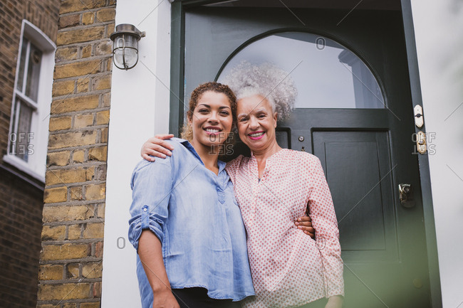 Portrait of senior female with daughter outside home
