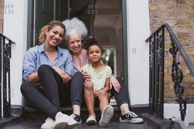 Three generations of women sitting outside family home