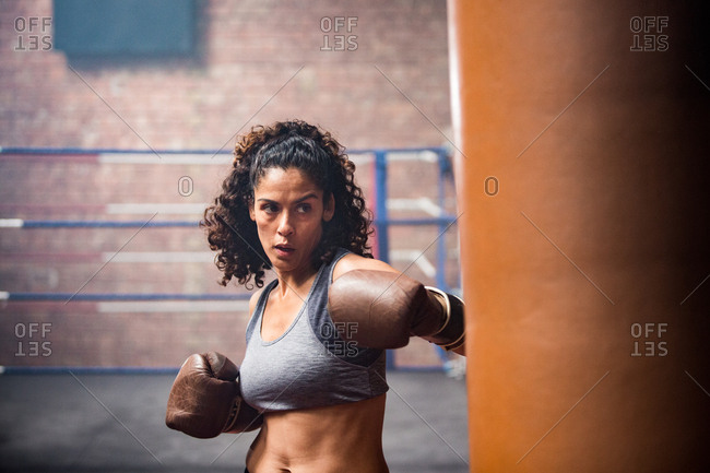 Female boxer punching a punch bag