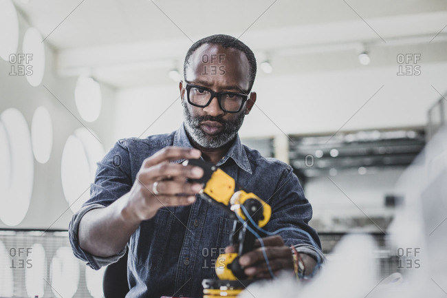 Closeup of African American adult male working on robotics