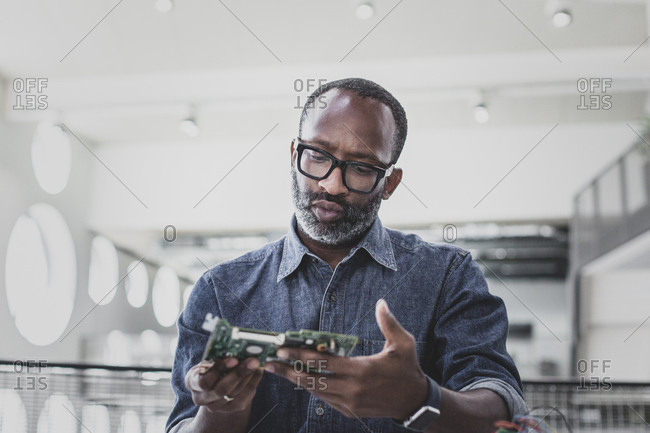 Closeup of African American adult male computer engineer holding motherboard
