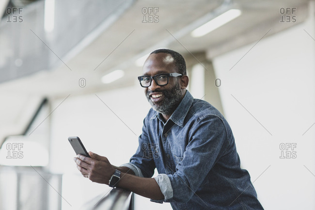 Portrait of african american male executive holding a smartphone