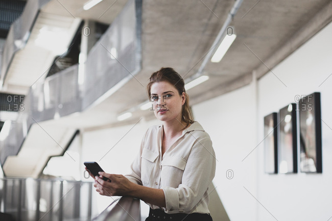 Portrait of female executive holding a smartphone