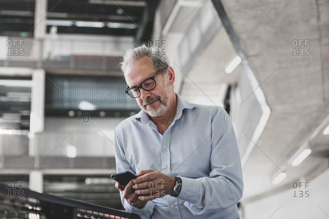 Mature businessman using smartphone