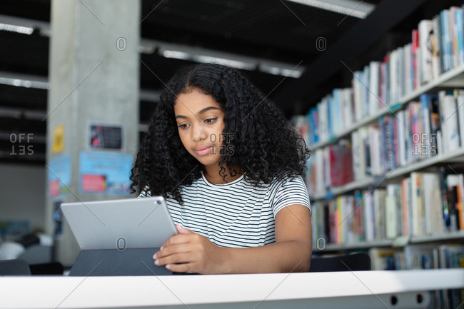 High school african american female student studying with digital tablet in library