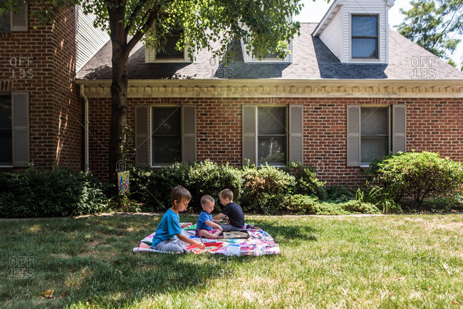 3 boys on a quilt in front yard of brick house doing school work