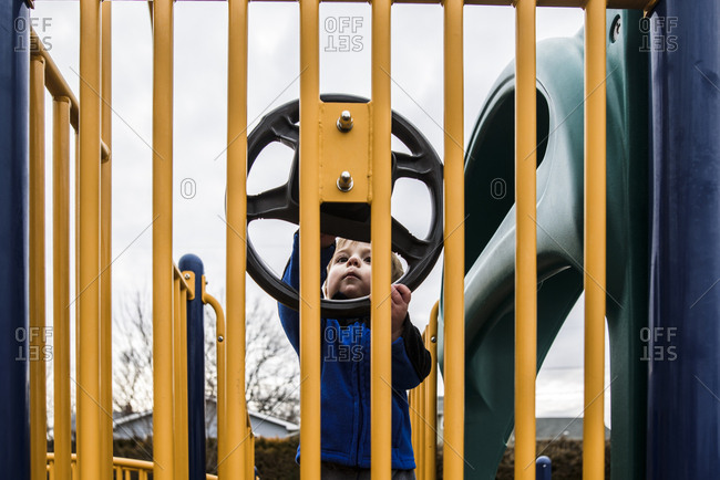 Toddler on playground looking curiously at play steering wheel