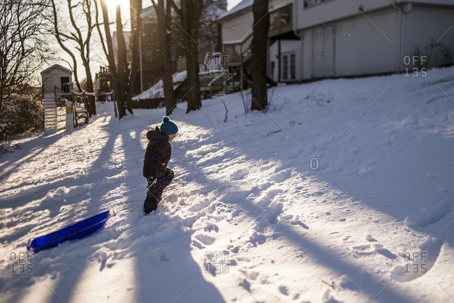 boy with hat on pulls blue sled up snowy hill as sun sets behind him