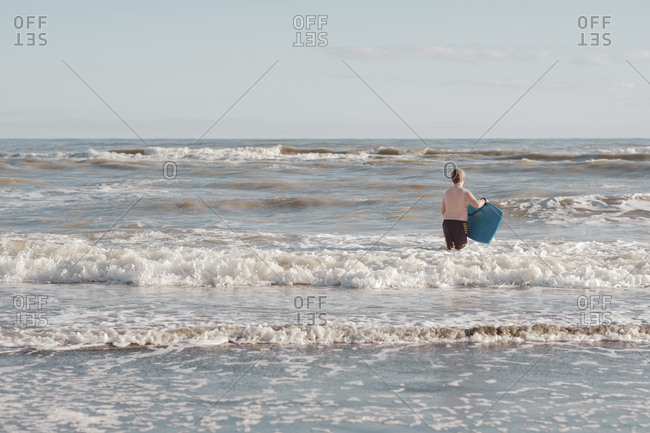Boy with boogie board in the water at the beach