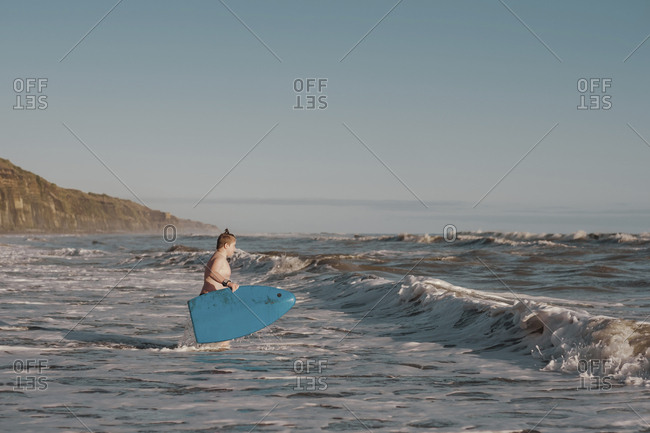 Young boy with boogie board at the beach