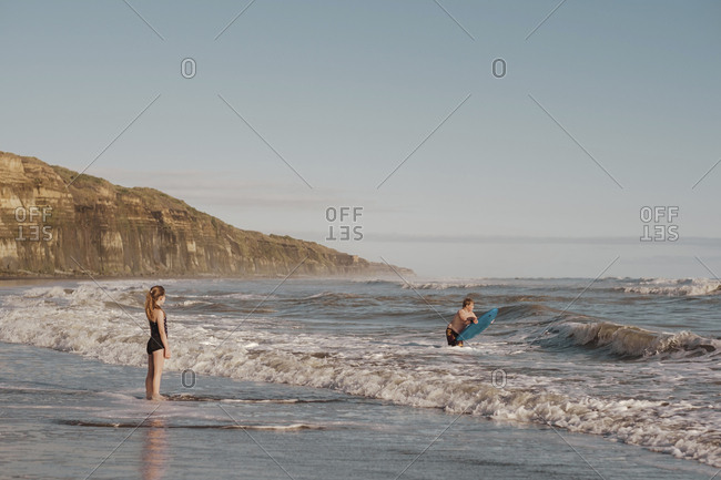 Boy with boogie board and girl in the water at the beach
