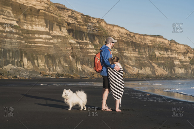 Father with arm around daughter at the beach with their dog
