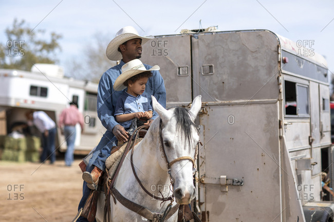 United States, Arizona, Chandler - March 9, 2019: A father and son on a horse at the Arizona Black Rodeo
