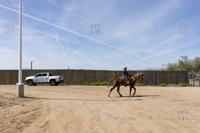 United States, Arizona, Chandler - March 9, 2019: A young cowgirl rides her horse alone backstage at the Arizona black rodeo