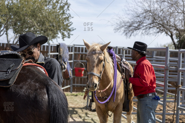 United States, Arizona, Chandler - March 9, 2019: Cowboys prepare their horses backstage at the Arizona black rodeo