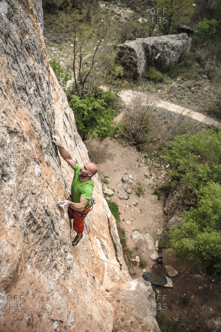 Mid aged strong sport climber climbing a limestone wall in Cuenca City