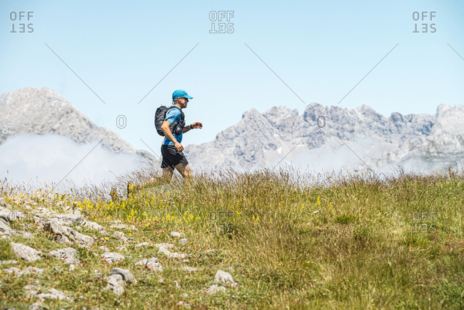 Trail runner running in the meadows close to Picos de Europa