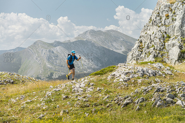 Mid adult runner running in the mountains on clear day