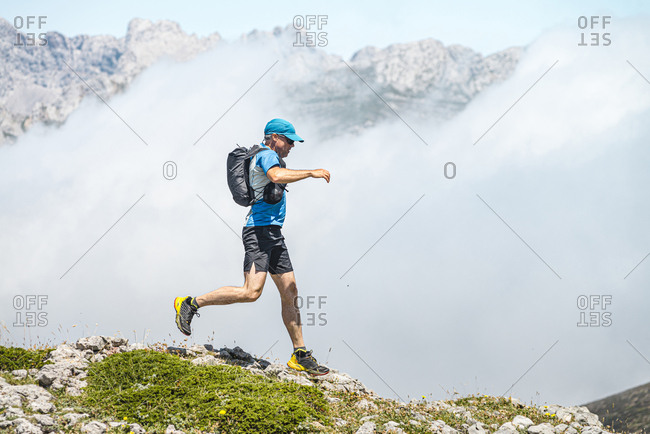 Trail runner jumping on foggy day close to Picos de Europa