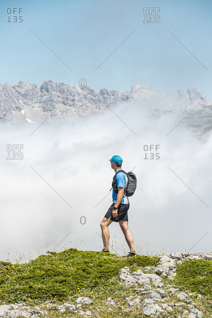 Rear view of a trail runner looking to Picos de Europa on foggy day