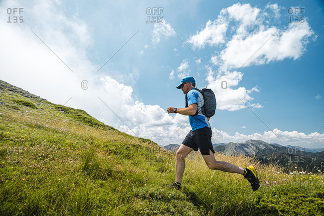 Trail runner running uphill in the meadows close to Picos de Europa