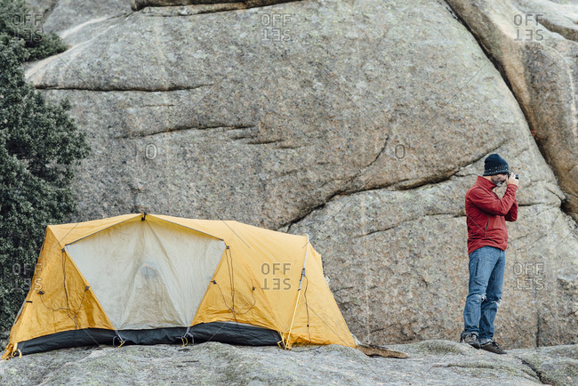 Mountain hiker taking pictures with digital camera close to tent