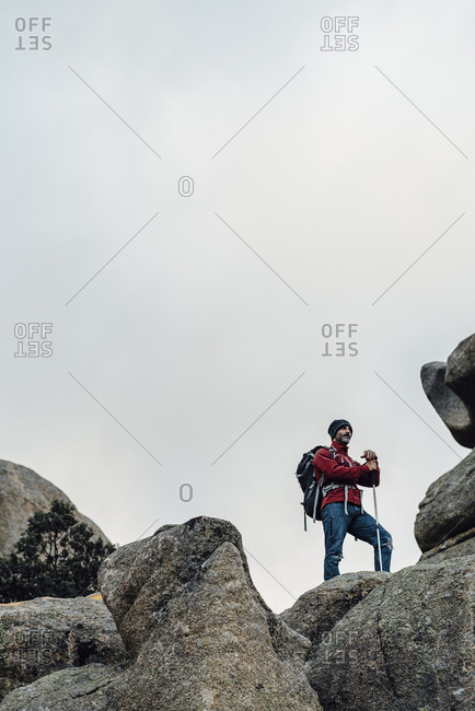 Low angle view of mid aged hiker in rocky scenery on cloudy day