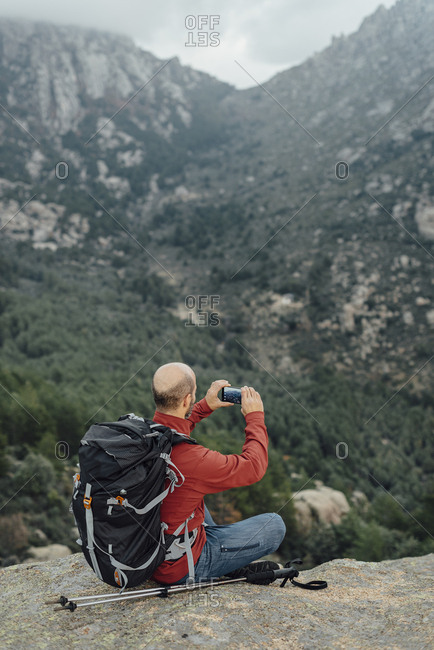 Mid aged bald hiker taking picture with smartphone to rocky scenery
