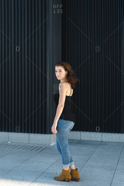 Side view of stylish woman in tank top and hair blow close to building