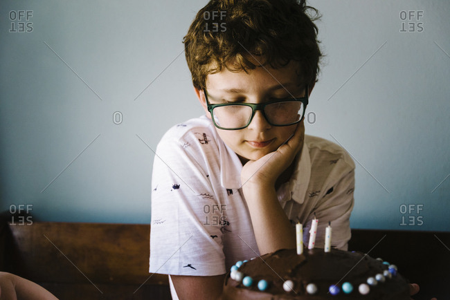 Tween boy admiring his birthday cake after decorating it.