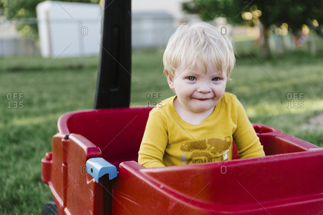 Male toddler sitting in a red wagon in family backyard.