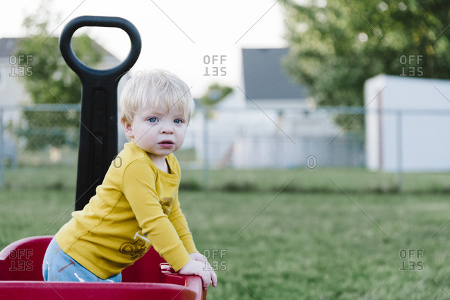 Toddler boy standing in a red wagon wearing a yellow shirt.
