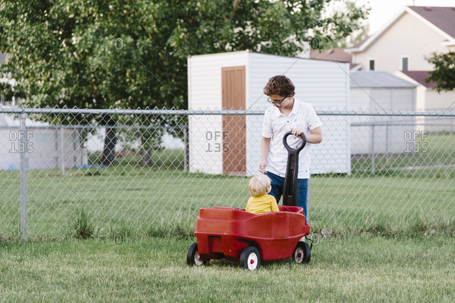 Tween pulling a toddler in a wagon in the backyard.