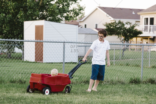 Tween pulling his nephew in a wagon in the family backyard.