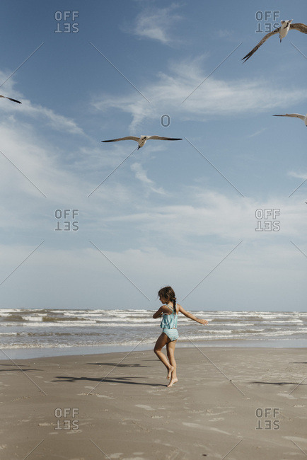 Girl twirling on beach with seagulls in Corpus Christi Texas