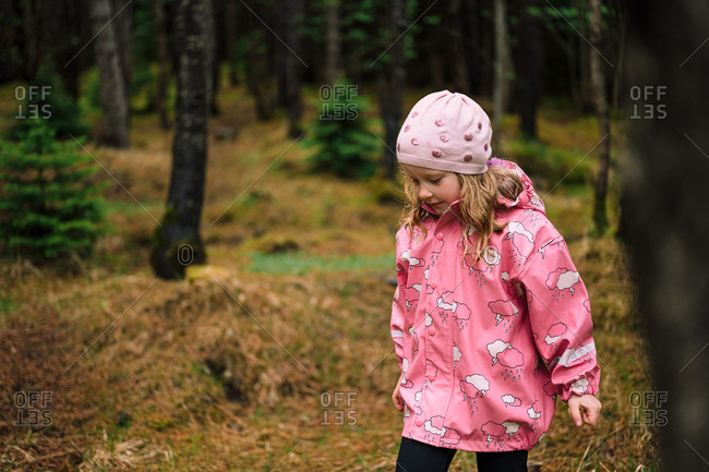 Little blond girl in coniferous forest