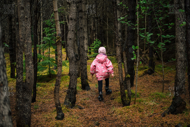 Girl walking in mossy old forest