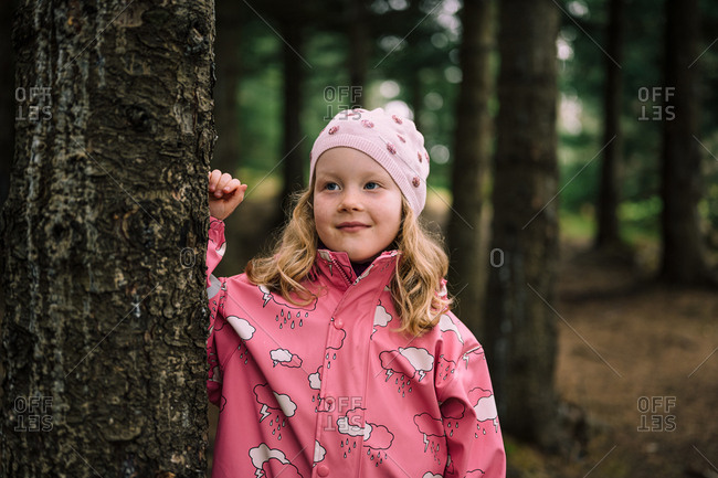 Blonde haired child in pink clothes leaning on tree