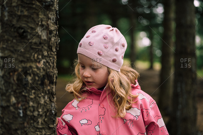 Blonde child in pink clothes in forest