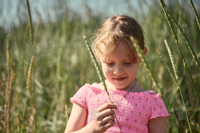 Shy girl with blade of grass in Iceland