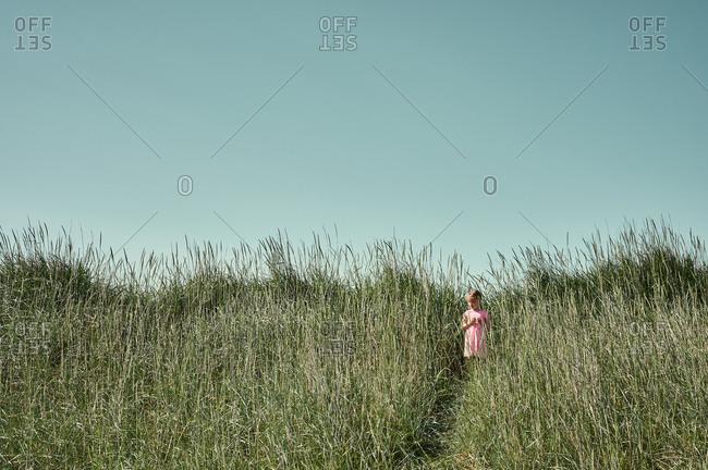 Little girl on serene green field  in Iceland