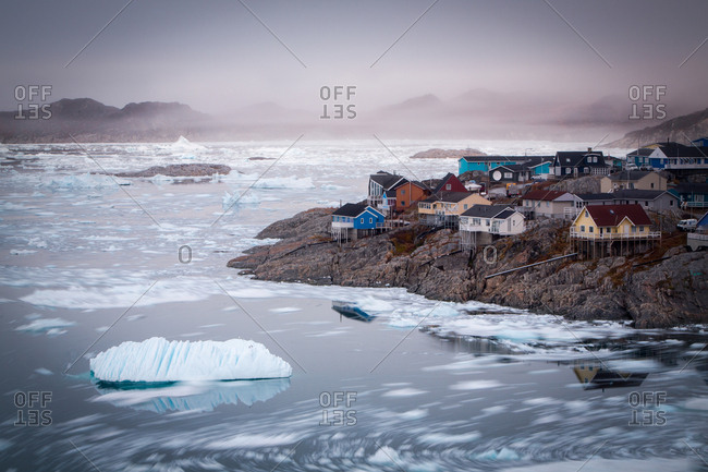 Iceberg offshore of colorful town of Ilulissat in the evening